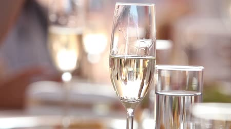 champagne bottles : The waiter pours champagne in wineglass, in a restaurant, The waiter pours champagne in crystal glasses, Restaurant interior
