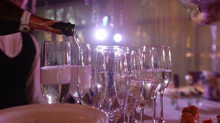 champagne bottles : The waiter pours champagne in wineglass, in a restaurant, The waiter pours champagne in crystal glasses