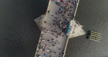 vertically : Tourists stroll along the Charles Bridge in Prague, Panoramic view from above, Vltava River, flight over the Charles Bridge, Prague