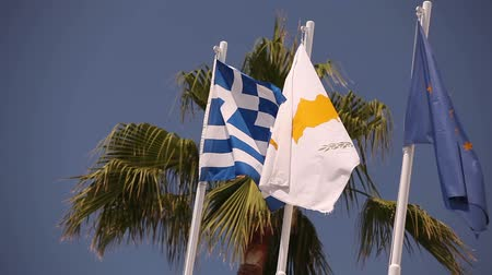 convento : Flags of the European Union, Greece, Cyprus, the city of Aya Napa, Greece, Flags on the flagpole, the wind waving the flag, Flags on flagpole, wind waving flag, against blue sky background