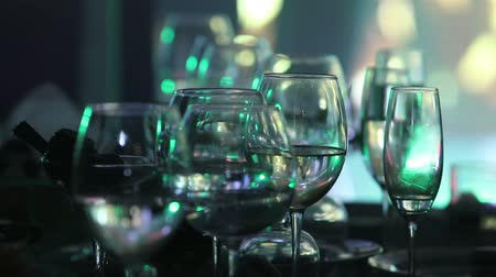 garfos : Glass glasses on a table in a restaurant, stage lighting, on background, dark, shallow depth of field, close-up