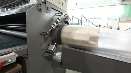 colchão : The mattress unit is supplied under a hydraulic press and compressed, hydraulic press compresses and wraps the mattress in cellophane, factory mattresses Stock Footage