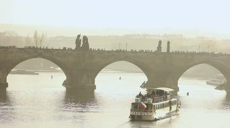 cseh : Tourists on Charles bridge, Charles bridge. Prague against the backdrop of a tourist ship at sunset Stock mozgókép