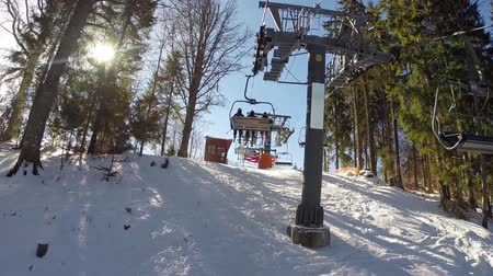 winda : a ski lift carries people up on the mountain, Skiers descend from the snowy mountains, people are skiing, high spruces on the hillside, sunny day, Wideo