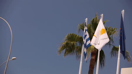 kypr : Flags of the European Union, Greece, Cyprus, the city of Aya Napa, Greece, Flags on the flagpole, the wind waving the flag, Flags on flagpole, wind waving flag, against blue sky background