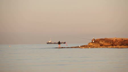 fenerbalığı : A fisherman is fishing in the sea at dawn, A fisherman on the rock against dawn sky, Silhouettes of fishermen with fishing rods on the beach. Man fishing at dawn on sea shore. Ship in the sea.
