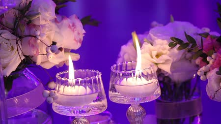 cintilante : Decorative candles on the table, glasses and Christmas candles on the table, wedding decorations, white wax candleswith glass candlestick, Candle with Glass Candlestick, restaurant, interior, close-up Stock Footage