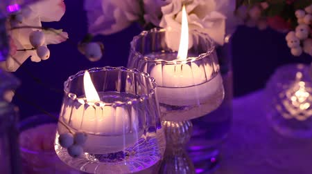 cera : Decorative candles on the table, glasses and Christmas candles on the table, wedding decorations, white wax candleswith glass candlestick, Candle with Glass Candlestick, restaurant, interior, close-up Stock Footage