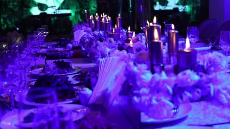 cutlery : Decorative candles on the table, glasses and Christmas candles on the table, wedding decorations, white wax candleswith glass candlestick, Candle with Glass Candlestick, restaurant, interior, close-up Stock Footage