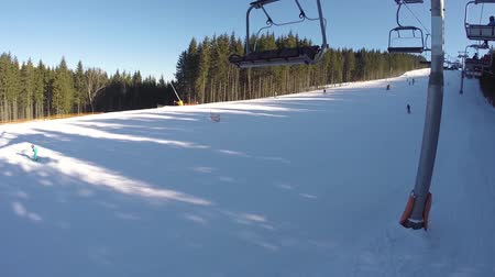 chairlift : A ski lift carries people up on the mountain. Skiers descend from the snowy mountains. People are skiing, high spruces on the hillside, sunny day Stock Footage