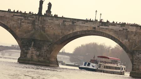 középkori : The Charles Bridge in Prague, excursion ship on the Vltava River against the background of the Charles Bridge, the movement of sightseeing cruises along the river, Prague, October 19, 2017