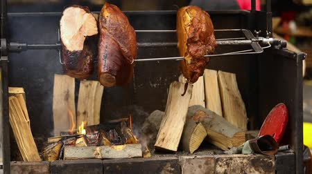cozinhado : Large chunks of delicious pork hams cooked on an open fire. The street food. Food outdoors. Camping and cooking on a spit over the fire, man cooks large pieces of meat on a spit on fire, closeup