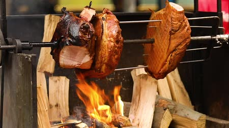 fry : Large chunks of delicious pork hams cooked on an open fire. The street food. Food outdoors. Camping and cooking on a spit over the fire, man cooks large pieces of meat on a spit on fire, closeup