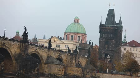 Чарльз : The Charles Bridge on the background of the old tower and the green dome of the cathedral in Prague, side view, tourists stroll along the Charles Bridge, Prague, October 19, 2017 Стоковые видеозаписи