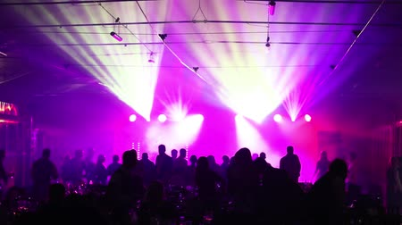 tancerze : a youth party in a restaurant or a nightclub, banquet tables with alcohol and food against the background of silhouettes of dancing people, stage light and purple fill Wideo