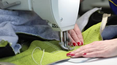szycie : woman working at a sewing machine, two-needle sewing machine, red manicure on female hands, Slow Motion Video, close-up, shallow depth of field Wideo