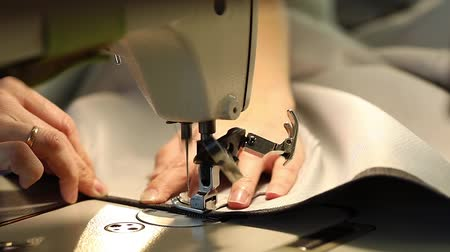 szycie : Woman working at a sewing machine, needle sewing machine, female hands, Slow Motion Video, close-up, shallow depth of field
