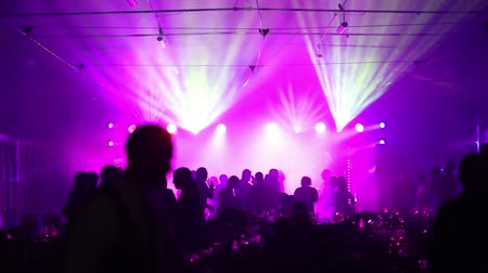 energický : A youth party in a restaurant or a nightclub, banquet tables with alcohol and food against the background of silhouettes of dancing people, stage light and purple fill