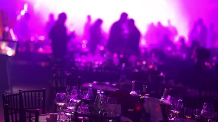tancerze : A youth party in a restaurant or a nightclub, banquet tables with alcohol and food against the background of silhouettes of dancing people, stage light and purple fill