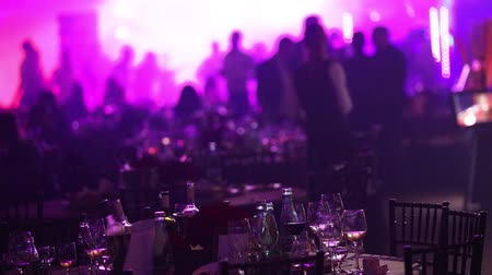 energický : a youth party in a restaurant or a nightclub, banquet tables with alcohol and food against the background of silhouettes of dancing people, stage light and purple fill Dostupné videozáznamy