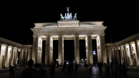 tor : Night view of the Brandenburg Gate in Berlin, people are walking in the square, Germany at night, Berlin