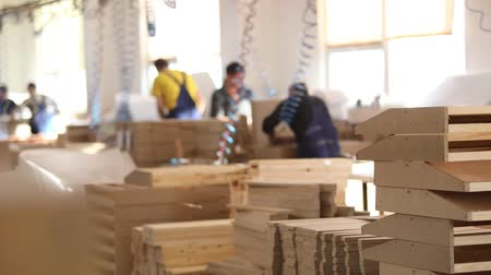 blurring : Furniture factory workers in yellow overalls collect furniture, Furniture manufacture,, industrial interior Stock Footage