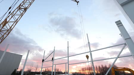 post and beam construction : Industrial exterior, Mounting of metal structures against the background of an orange sky with clouds, construction work, construction of an industrial building, timelapse Stock Footage