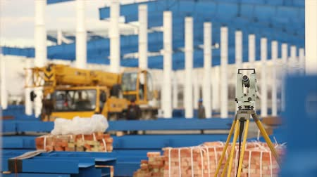 geodesy : Optical Theodolite, Builders Theodolite, construction theodolite on the background of the construction of a large industrial building or warehouse, construction work