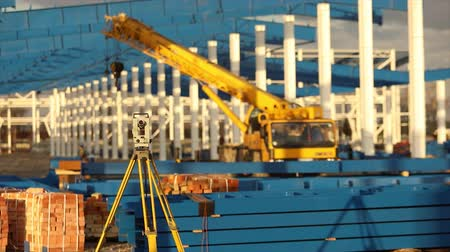 field measurements : Optical Theodolite, Builders Theodolite, construction theodolite on the background of the construction of a large industrial building or warehouse, construction work