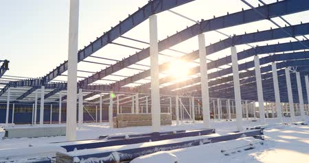 construction crane : Construction of a modern factory or warehouse, modern industrial exterior, panoramic view, Modern storehouse construction site, the structural steel structure of a new commercial building Stock Footage