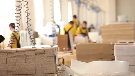 blurring : Furniture factory workers in yellow overalls collect furniture, Furniture manufacture,, industrial interior,small depth of field