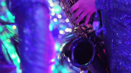 saxofone : A girl with a saxophone, a musical group of girls with a saxophone perform on stage, a blue dress, a stage light, a movement, closeup, nightclub, restaurant Vídeos