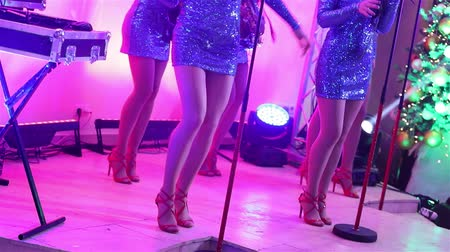 szakszofon : A female music band performs on stage, Beautiful Girls with saxophones on stage. Girl playing saxophone, beautiful female feet, womens legs in red high-heeled shoes