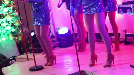 mikrofon : A female music band performs on stage, Beautiful Girls with saxophones on stage. Girl playing saxophone, beautiful female feet, womens legs in red high-heeled shoes