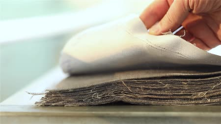 decorador : Samples of fabric for upholstery the furniture, a stack of furniture fabrics on the table, fabric furniture, business designer hands, close-up, shallow depth of field Stock Footage