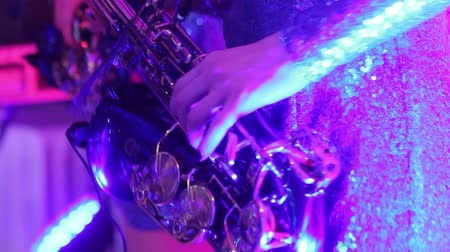 saxofone : A girl with a saxophone, a musical group of girls with a saxophone perform on stage, a blue dress, a stage light, a movement, closeup, nightclub, restaurant Stock Footage