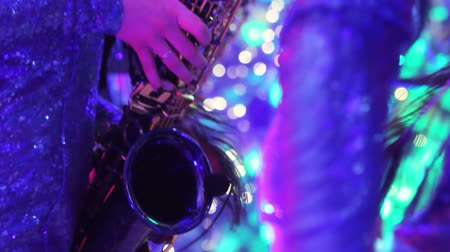 szakszofon : A girl with a saxophone, a musical group of girls with a saxophone perform on stage, a blue dress, a stage light, a movement, closeup, nightclub, restaurant Stock mozgókép