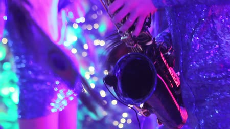 scena : A girl with a saxophone, a musical group of girls with a saxophone perform on stage, a blue dress, a stage light, a movement, closeup, nightclub, restaurant Wideo