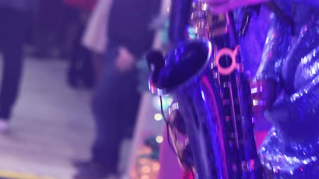 trumpet : A girl with a saxophone, a musical group of girls with a saxophone perform on stage, a blue dress, a stage light, a movement, closeup, nightclub, restaurant Stock Footage