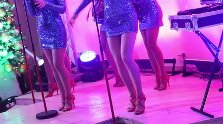 saxofon : A female music band performs on stage, Beautiful Girls with saxophones on stage. Girl playing saxophone, beautiful female feet, womens legs in red high-heeled shoes