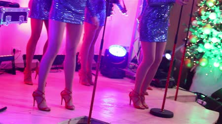 saxofone : A female music band performs on stage, Beautiful Girls with saxophones on stage. Girl playing saxophone, beautiful female feet, womens legs in red high-heeled shoes