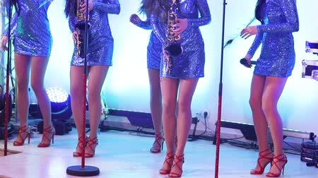 high heel shoe : A female music band performs on stage, Beautiful Girls with saxophones on stage. Girl playing saxophone, beautiful female feet, womens legs in red high-heeled shoes