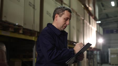 supervisor : Focused warehouse manager writing on clipboard in a large warehouse, warehouse worker, industrial interior, a warehouse interior Stock Footage