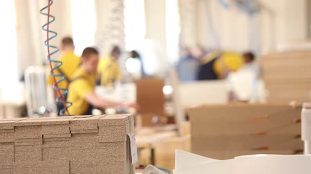 продукт : Furniture factory workers in yellow overalls collect furniture, Furniture manufacture,, industrial interior,small depth of field