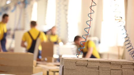 shops : Furniture factory workers in yellow overalls collect furniture, Furniture manufacture,, industrial interior,small depth of field