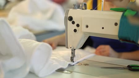 denim : Sewing machine and white fabric, woman hand behind sewing, hand female, sewing manufacture, garment factory, woman working at a sewing machine