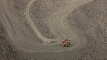old pit : A large tipper digs through a career, an industrial truck dredges cargo in its quarry, a large yellow dumper