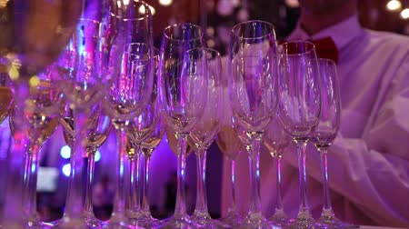 alkol : The waiter pours champagne in glasses, Glasses with champagne on the table in the restaurant, glasses of champagne on festive table, Clean glasses on a table prepared by the bartender for champagne