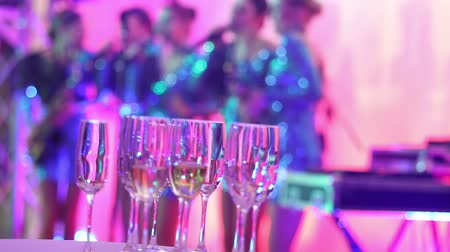 alkol : Glasses with champagne on the background of silhouettes of womens music group, a female music band performs in a restaurant or hotel lobby