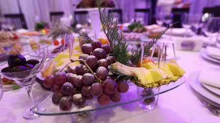 előételek : Fruit and food on the banquet table in the restaurant, pieces of pineapple and bunches of grapes on the banquet table, decoration of the banquet hall, restaurant interior